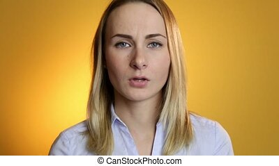 A cute young white woman makes a sad face on a yellow...