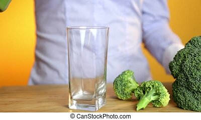 Young woman pouring a healthy green smoothie on a glass