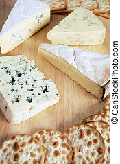 Four gourmet cheeses with biscuits on a cheeseboard.