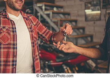 Guys at the motorbike repair shop - Handsome man is giving a...