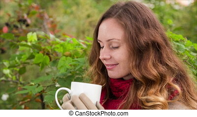 Adorable girl are drinking from cup a hot beverage in autumn...