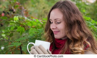 Dreaming girl are drinking from cup a hot beverage in autumn...