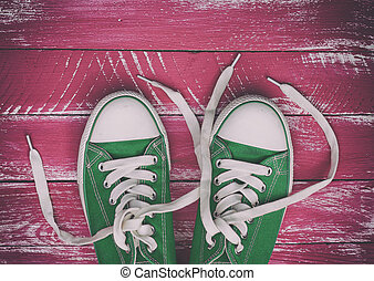 pair of worn sneakers on a pink green old wooden surface