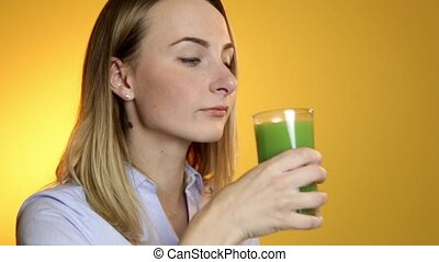 Young woman drinking green vegetable smoothie.