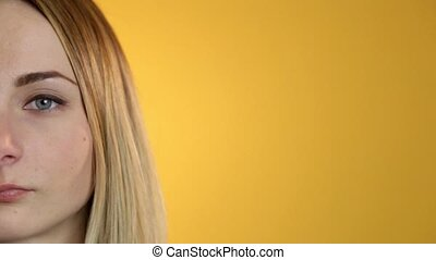 Young woman portrait close up half face character series isolated on a yellow background