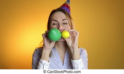 Beautiful girl blowing balloons on a yellow background