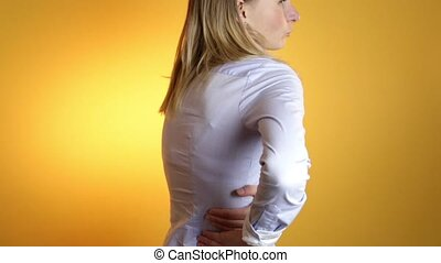 A close up of a woman back who is dealing with backache. - A...
