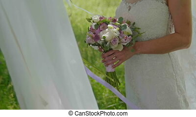 Bride at meadow outdoor holding her wedding bouquet in slow motion