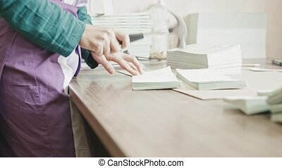 Woman complements the pages of the brochure with a hammer at...