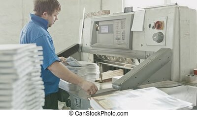 Worker in blue jacket worker puts the paper in the cutter guillotine machine in a printing factory, slider