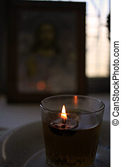 Candle and icon in church - A candle burning in front of an...