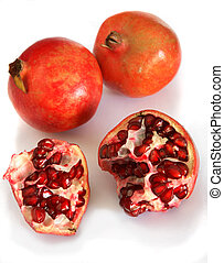 Pomegranates - A group of ripe pomegranates over white, one...