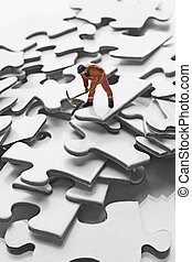 worker figurine on puzzle pieces - worker figurine on pile...