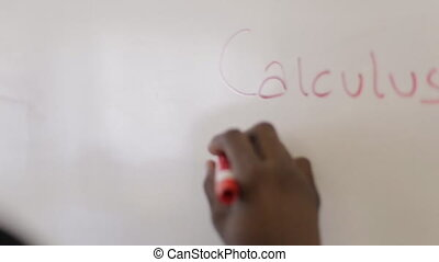 Man writes on a white board marker - Student giving a...