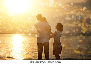 Family enjoying holiday vacation on beach in sunset