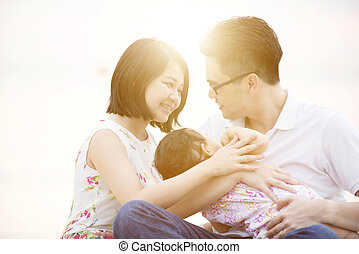 Family enjoying quality time - Young Asian family outdoor...