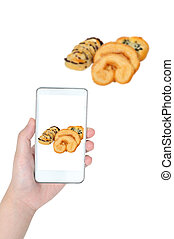 Woman hand holding smart phone taking pastry product