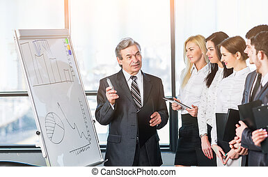 Head of business team explains to his colleagues the methods...