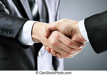 Photo of handshake  business partners after signing promising contract on a black background