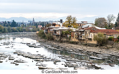 Wrecked buildings of Kutaisi, mountain river in centre, Georgia