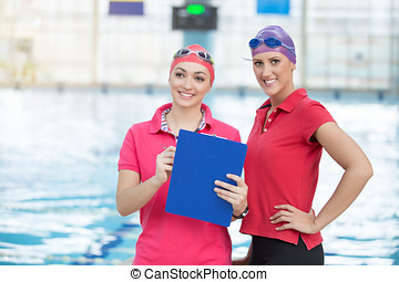 Fit female swimming trainer with tablet at the pool.