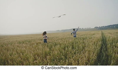 Young couple - man and woman running with kite on meadow of ears wheat