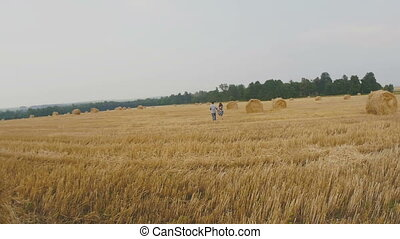 Beautiful Young Couple in Love go for a romantic walk in meadow with haystacks