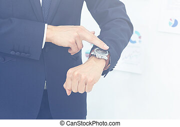 idea is to save time. businessman pointing at his wristwatch
