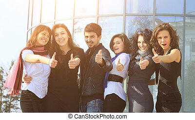 group of college students smiling friendly standing next to...