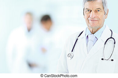 Portrait of an experienced physician in age, in background work team.
