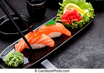 Japanese cuisine. Salmon sushi nigiri on a black plate with...