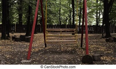 Empty swings swaying at playground.