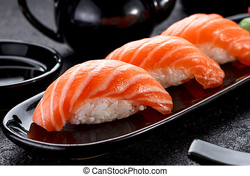 Salmon sushi with soy sauce on a black plate and dark...