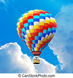 Color hot air balloon in the blue sky with clouds - Creative...
