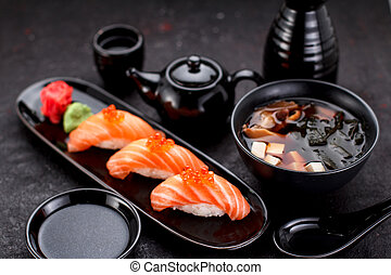 Japanese cuisine. Salmon sushi nigiri and miso soup on black...