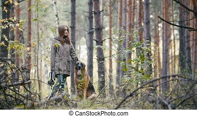 Young pretty cute woman walking in autumn forest with her...