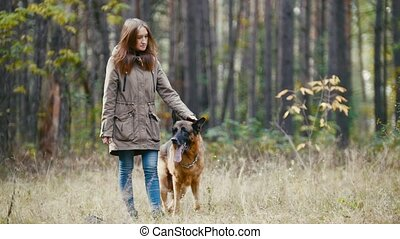 Young woman standing with a shepherd dog in autumn forest -...