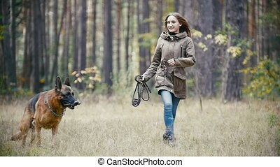 Young woman holding a leash running with a shepherd dog in autumn forest, slow motion