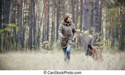 Young woman running with a shepherd dog in autumn forest,...