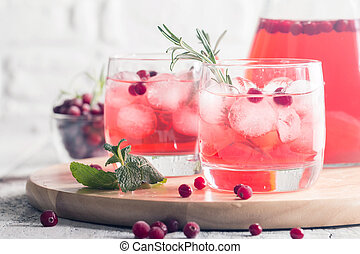 Refreshing drink with cranberries, ice and rosemary on white...