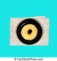 Plain donut with sugar in black plate on napery, pastel...