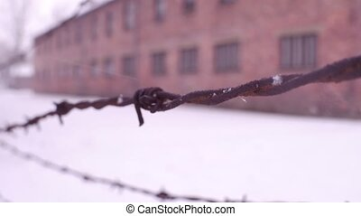 Close-up shot of old rusty barbed wire fence in former...