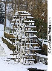 Small waterwheel in frozen creek in park - Small waterwheel...