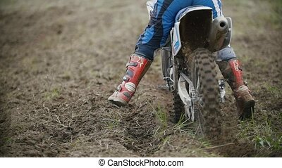 Motocross racer start riding his dirt Cross MX bike kicking...
