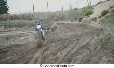 Slow motion: Motocross racer jumping. Rear view of biker on...