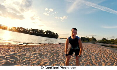 Male runner at the beach takes a break to get his breath...
