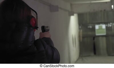 Woman shooting with a gun in shooting gallery. Slow-Motion -...