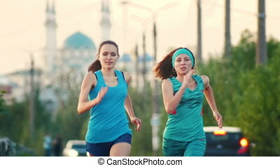 Two young beautiful woman running at city park , the mosque in the background, slow-motion, close-up