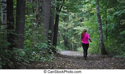 Runner young woman running in autumn park exercising...