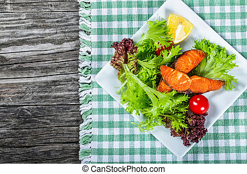 healthy salad with grilled salmon fish, top view